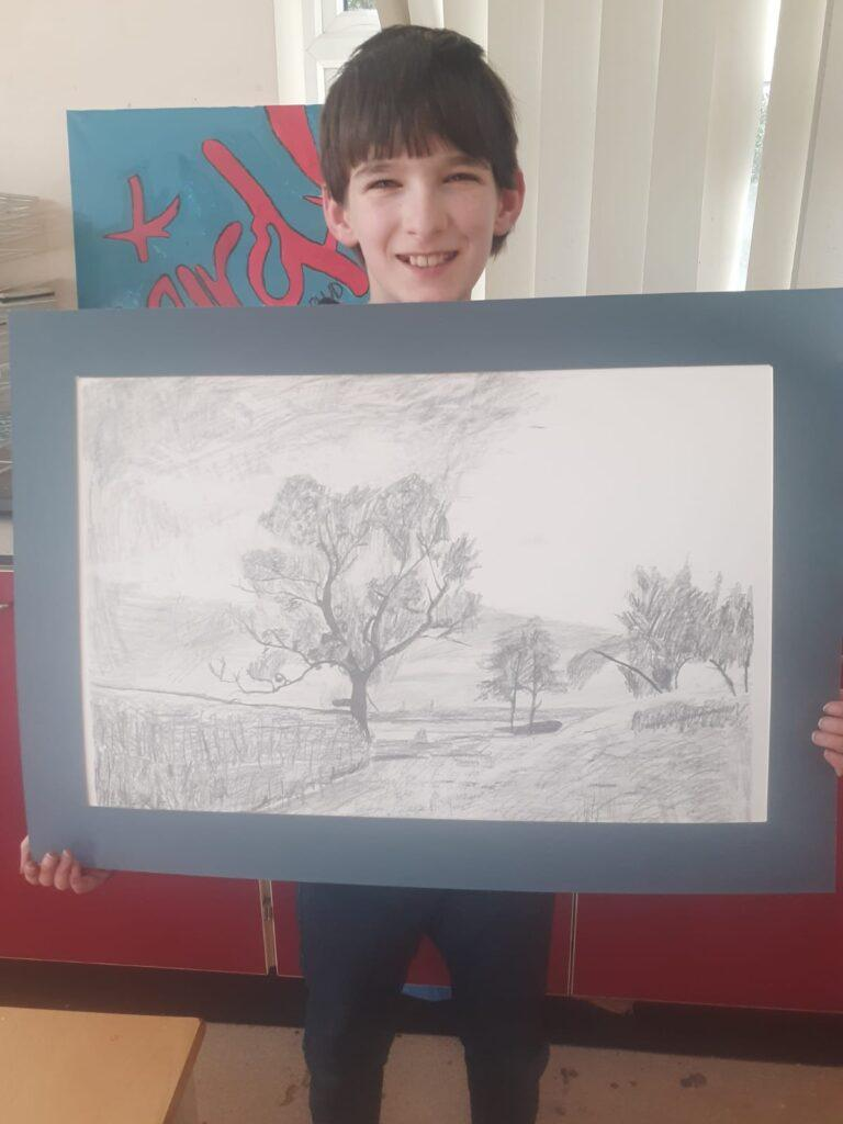 A child holding his lovely drawing at summer camp