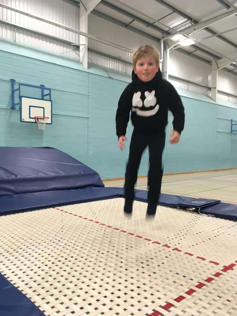 A child jumping on a trampoline at summer camp
